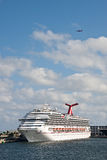 Luxury Cruse Ship at Dock with Airplane Overhead Royalty Free Stock Photo