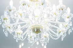 Luxury crystal chandelier on the celling with lit lamps royalty free stock images