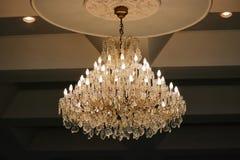 Luxury crystal chandelier hanging under ceiling in the room. Luxury crystal chandelier hanging under ceiling in the room Royalty Free Stock Photography
