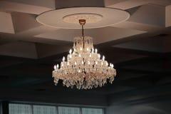 Luxury crystal chandelier hanging under ceiling in the room. Luxury crystal chandelier hanging under ceiling in the room Royalty Free Stock Images