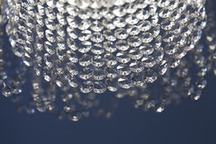 Luxury crystal chandelier with pendant decor retro style. blue background, soft focus, macro view. Glamour interior Stock Image