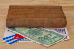Luxury Cuban cigars and money on the wooden desk Stock Photos