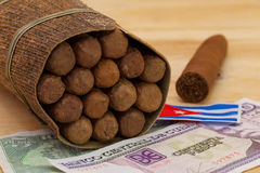 Luxury Cuban cigars and money on the wooden desk Royalty Free Stock Image
