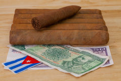 Luxury Cuban cigars and money on the wooden desk Royalty Free Stock Photography