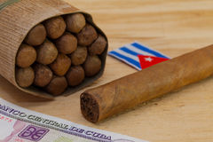 Luxury Cuban cigars and money on the wooden desk Royalty Free Stock Photo