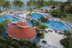 Luxury Curvy Hotel Swimming Pool Aerial View. Luxury swimming pool at a 5 star hotel by the ocean, with in-pool jacuzzi and sun loungers royalty free stock photo