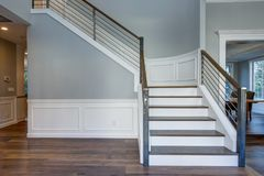 Luxury custom built home interior. Stunning two story entrance foyer design with white wainscoting, grey walls and a white staircase stock image