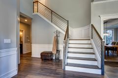 Luxury custom built home interior. Stunning two story entrance foyer design with white wainscoting, grey walls and a white staircase royalty free stock images