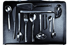 Luxury cutlery set on leather suitcase. Elegant and luxury set of silver cutlery arranged on black leather suitcase Royalty Free Stock Photos