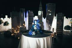 Luxury dark three leveled wedding cake decorated with blue hydrangeas. Artwork. Wedding decoration. Stock Photography