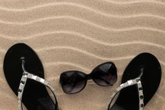 Luxury, decorated with rhinestone beach flip flops and sunglasses. Lying on sand dunes royalty free stock photography
