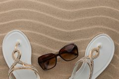 Luxury, decorated with rhinestone beach flip flops and sunglasses. Lying on sand dunes stock photography