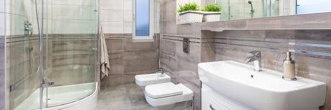Luxury design bathroom. Panorama of luxury design bathroom in beige with basin, mirror, toilet, bidet and big shower royalty free stock photo