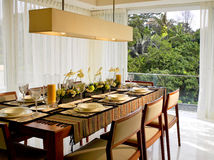 Luxury dining room. Dining room in luxury home with view of the trees outside Royalty Free Stock Image