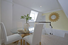 Luxury dining room with round glass table. White chairs and a flower Stock Photo