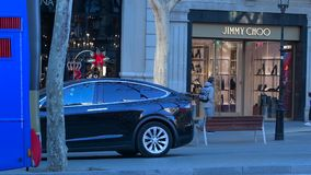 Luxury electric black Tesla car parked Jimmy Choo. Barcelona, Spain - Circa 2019: Luxury electric black Tesla car parked in front of Jimmy Choo shoe store in stock video