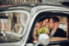 Luxury elegant wedding couple kissing and embracing in stylish b. Happy stylish newlywed couple posing in retro car Royalty Free Stock Photo