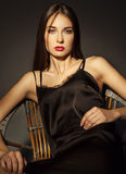 Luxury elegant woman in lace silk black dress sitting over dark Royalty Free Stock Photography