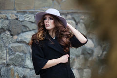 Luxury elegant woman in trendy black coat and hat standinf near. Brick wall. Beautidul lady in european look. Fashion vogue style Royalty Free Stock Photography