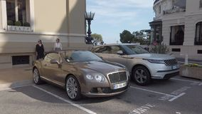 Luxury English Cars Parked In Front Of Monte-Carlo Casino In Monaco. Monte-Carlo, Monaco - June 20, 2019: Luxury English Cars Bentley Continental GTC, Land Rover stock video