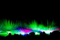 Colorful laser show nightlife club stage with smartphone filming. Luxury entertainment with audience silhouettes in nightclub event, festival or New Year`s Eve royalty free stock photography