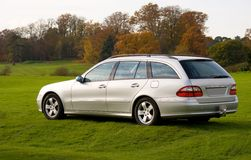 Luxury estate (wagon) car parked on grass. Prestige silver car parked on grass Royalty Free Stock Photography
