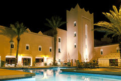 Luxury exotic hotel. A luxury exotic hotel with a large swimming pool at night stock photos