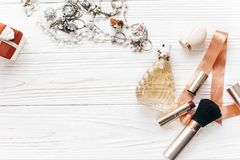 Luxury expensive jewelry and make up essentials and perfume flat. Lay on white rustic wooden table with space for text in soft morning light. fashion blogger Stock Photo