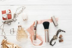 Luxury expensive jewelry and make up essentials and perfume flat. Lay on white rustic wooden table with space for text.  fashion blogger. modern woman set of Stock Image
