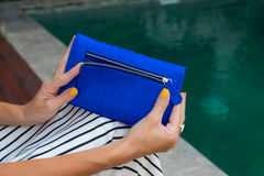 Luxury fashion snakeskin python wallet in woman hands outdoors, shoot near the swimming pool, Bali. Stock Photography