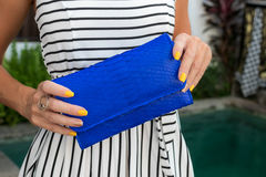 Luxury fashion snakeskin python wallet in woman hands outdoors, shoot near the swimming pool, Bali. Royalty Free Stock Image