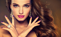 Luxury fashion style.Brunette with long curled hair Stock Photos