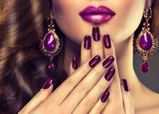 Luxury fashion style, nails manicure. Luxury fashion style, nails manicure, cosmetics ,make-up and curly hair . Makeup in shades of purple and violet earrings Royalty Free Stock Images