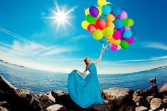 Luxury fashion stylish woman with balloons in hand on the beach Royalty Free Stock Image