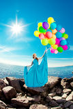 Luxury fashion stylish woman with balloons in hand on the beach Stock Image