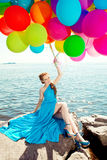 Luxury fashion stylish woman with balloons in hand on the beach Stock Photography