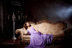 Luxury fashion stylish woman in the rich interior. Beauty girl w Stock Photos