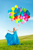 Luxury fashion woman with balloons in hand on the field against royalty free stock photography