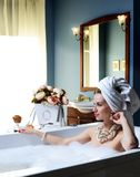 Luxury fashion woman in hotel spa lying in bath tub with bouquet of flowers Stock Images