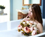 Luxury fashion woman in hotel spa lying in bath tub with bouquet of flowers Royalty Free Stock Photos