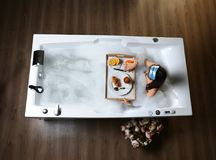 Luxury fashion woman in the morning take breakfast in hotel spa lying in bath tub Stock Photography