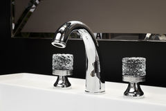 Luxury faucet mixer with crystal handles on a white sink in a beautiful dark bathroom Stock Photos