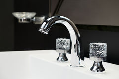 Luxury faucet mixer with crystal handles on a white sink in a beautiful dark bathroom Stock Image