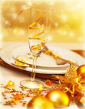 Luxury festive table setting. Picture of luxury festive table setting, closeup image of beautiful white utensil decorated with golden shiny balls and candle on Stock Photo