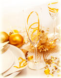 Luxury festive table setting. Picture of luxury festive table setting, closeup image of beautiful white utensil decorated with golden shiny toys and candle Stock Image
