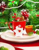 Luxury festive table setting. Picture of luxury festive table set, romantic candle with red tea cup and little Christmas decoration on white plate, green spruce Stock Photography