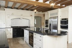 Luxury Fitted Kitchen In House With Beamed Ceiling Stock Photo