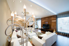 Luxury floor lamp in modern spacious living room with fireplace Stock Photography