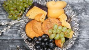 Luxury food concept. Cheese restaurant serving. Food art concept. Variety of hard cheese and branch of grapes on rarity. Silver plate put on wooden board stock video footage