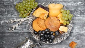 Luxury food concept. Cheese restaurant serving. Food art concept. Variety of hard cheese and branch of grapes on rarity. Silver plate put on wooden board stock video